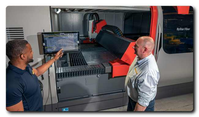 Two Econ staff members operate the new, £850,000 laser cutter